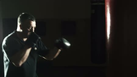 bokshandschoenen : Boxing Trainer training in de sportschool Stockvideo