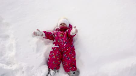 snow angel : The little girl falls on snow and laughs
