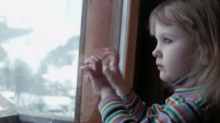 odráží : Little cute girl behind window in winter Dostupné videozáznamy