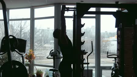 lift ups : silhouette of male bodybuilder pulling up in a gym