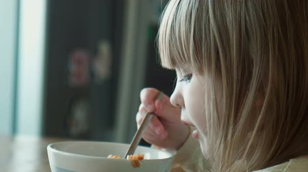 кукуруза : The little girl eats at a table