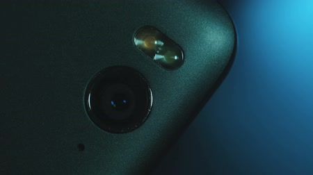 lighting up : Closeup of Smartphone Camera Module on the back, placed on blue gradient background