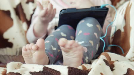 wanna : Legs, feet of the little girl sitting in a chair and watching video on the digital tablet