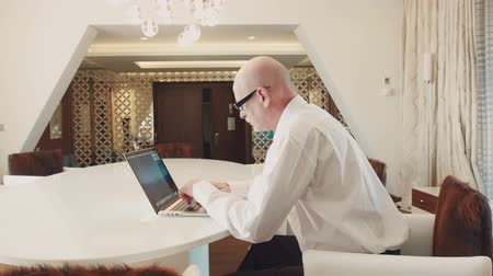 advokát : Senior successful businessman working at laptop in hotel apartments
