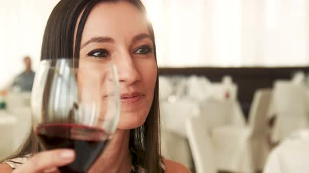 bebida alcoólica : Young brunette girl is very beautiful Spanish or Latin looks, smiles and looks at her husband or boyfriend and drinks red wine from a glass