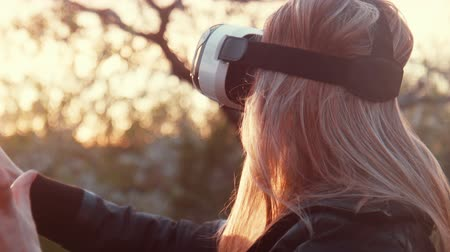 tektura : Girl outdoor, watching a video in 360 degrees virtual reality helmet.  VR equipment headset.