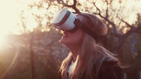 tektura : Young blonde insert the smartphone in a virtual reality helmet,  puts on shes head and looks 360 degrees video or playing a game Wideo