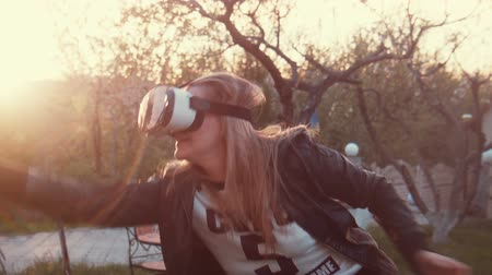 realidade : Young woman uses head-mounted display. Playing game using VR-helmet for smart phones.