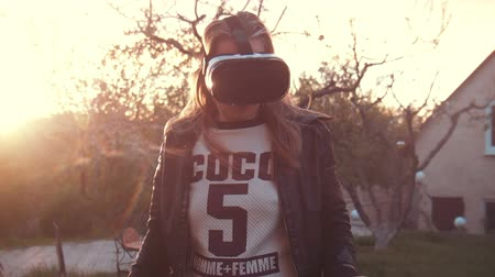 tektura : Girl uses head mounted display Oculus Rift outdoor at home.