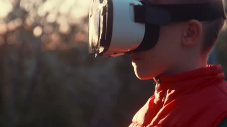 realidade : Little boy with surprise and pleasure uses virtual reality helmet and moves around itself outdoor Vídeos