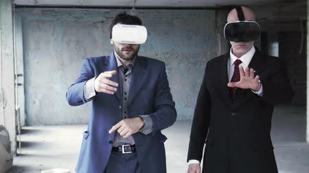 vestindo : Two businessmen in suits wearing on oculus rift and discussing something while gesturing