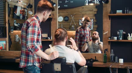 borbély : Bearded man showing to barber how to groom his beard in mirror