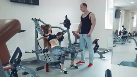 inclinado : Brunette young woman performing bench press exercise while trainer watching her technique