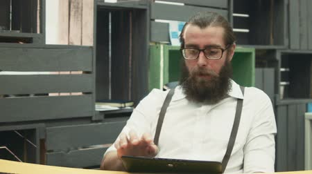 breaktime : Bearded worker in glasses at table finishing work and playing tablet
