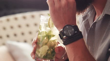 revitalizing : Man with watch and black leather bracelets sips an herbed drink from a tall glass