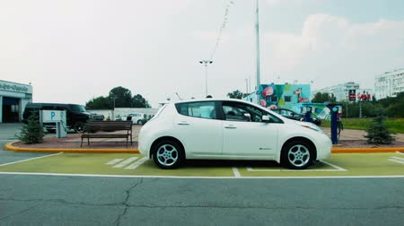 recharging : The approaching car to recharge station. Depot for recharging electric cars with two digital charging points in an urban environment conceptual of eco friendly transport. Man getting ready to charge his electric car standing at the charger with his white  Stock Footage