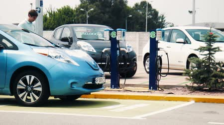 ekologia : Electric car power stations at parking lot with vehicles stopped in the background Wideo