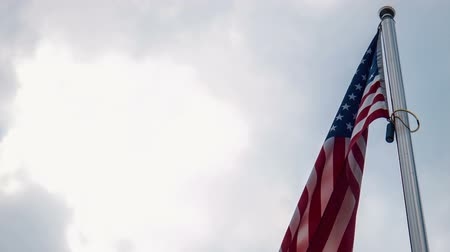 vlastenectví : United States American flag flying from a flagpole in a wind showing the stars and stripes against a cloudy blue sky in a patriotic image. View from low angle Dostupné videozáznamy