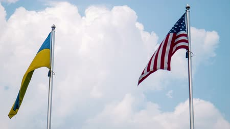 honesto : Ukraine and United States flags fluttering in wind with bright sky in background