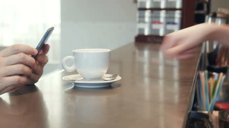 xícara de café : Waitress serving coffee to a man on a mobile phone passing the cup over the counter as he texts a message, close up of the hands
