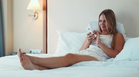 boso : Pretty blonde woman wearing nighty lying in bed on white bedsheet and use smartphone and laughing