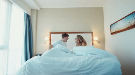 slept : Young couple having a raucous argument in bed yelling and shouting at each other in their sleepwear Stock Footage