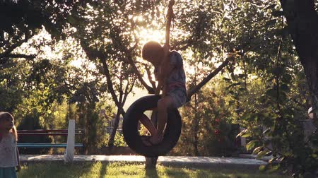 aydınlatmalı : close up, slow motion of happy girl and boy playing at park with tire swing hanging from tree with beautiful sunlight in background Stok Video