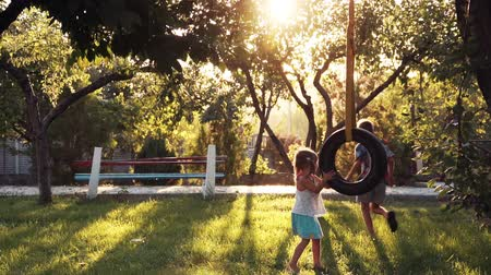 девушка : Slow motion of happy girl and boy playing at park with tire swing hanging from tree with beautiful sunlight in background