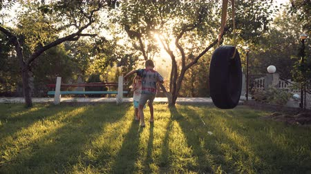 swing : Happy siblings running through park with tire swing hanging from tree and beautiful sunlight in background