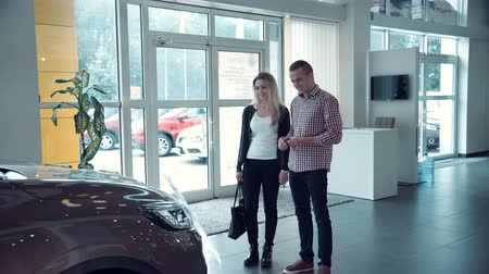 revendedor : Couple comes into Car dealership to choose the car to buy it. The sales manager approaches them and begins to tell about petrol and electric vehicles