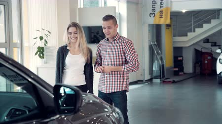 revendedor : Young Salesman Delivering Sales Pitch to Couple Buying New Vehicle inside Car Dealership While Standing in front of Shiny New Model of car or electrocar