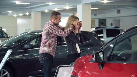samochód : Man Standing Behind Woman and Covering Her Eyes While Standing in front of Shiny New Red Vehicle Inside Car Dealership - Man Surprising Woman with New Car in Show Room.