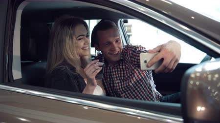 escolha : Excited young couple making a decision to purchase a new car sitting inside in a motor showroom checking it out for ownership and make selfie picture using smartphone.