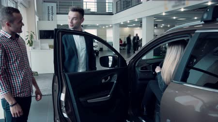revendedor : The car sales manager in a suit, suggests the client to sit down in the car to look at its interior and quality. Possibly it is sale of the electric vehicle