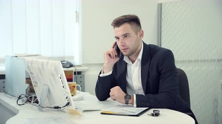 touched : Hardworking businessman typing on a computer as he sits at a table in a modern white office, side view and he has call by the phone there is bad news he is frustrated