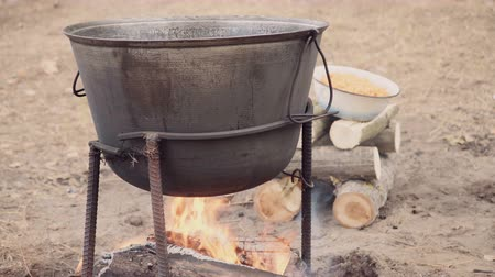 kavurma : Cooking soup with lamb in a cauldron on a wood stove in the autumn. A man is mixing braised lamb, onion and bell pepper in the cauldron.