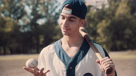 cabeça e ombros : Head and Shoulders Close Up of Young Man Wearing Baseball Cap and Jersey, Smiling with Eyes Closed While Holding Baseball Bat Over Shoulder in Field on Sunny Summer Day 4K