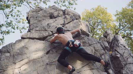 fissures : Shirtless young man rock climbing searching for hand holds on a rock face as he practices his sport on a mountain surrounded by leafy green trees.