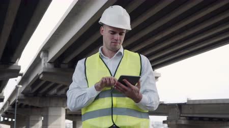 mérnök : 4K stabilized movement shot of Young engineer wearing white hard hat and yellow vest walking under the overpass and using tablet computer for photography Stock mozgókép