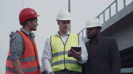 strukturální : 4K Workers in vests showing boss something on tablet computer while standing outside with tall street lamps behind them and demonstrating with hands.