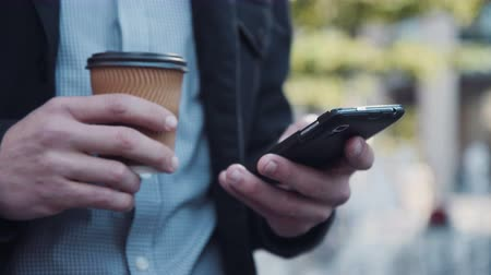 bilinmeyen : Businessman with small paper disposable cup of takeaway coffee using smartphones touch screen. Close up view of arms tapping it. Man texting on his mobile phone with a cup of coffee in a his hand, close up view