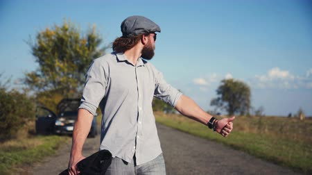 látszó el : Man in grey cap with beard and ponytail hitchhiking, taking off cap and looking at watch.
