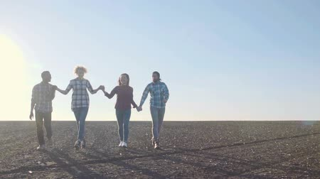 kutluyor : Slow motion of excited group of four teenagers in empty cultivated field under the blue sky jumping. Stok Video