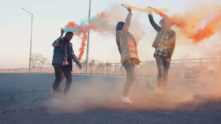 barevný : Four happy young mixed racial friends dancing on bridge in city at sunset in evening with colored smoke grenades. Urban environment Dostupné videozáznamy