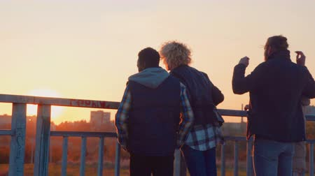 négy ember : Four different ethnicity friends hanging out on bridge at sunset.