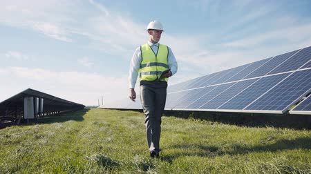 mérnök : Single man in reflective green vest and white hard hat with digital tablet, walking near solar panels for concept about employment in alternative energy