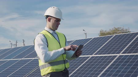 rendszer : Technician walks beside array of solar panels while wearing hard hat and holds computer digital tablet Stock mozgókép