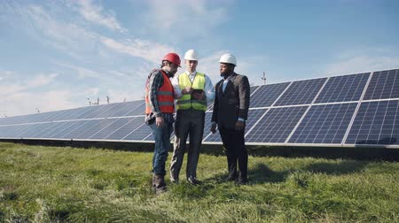 sürdürülebilir : Three adult mixed race male workers in reflective vests walking in between long rows of photovoltaic solar panels