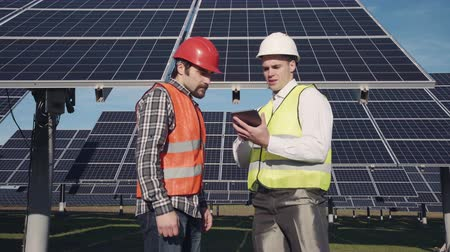 mérnök : Technicians in long sleeve shirts, reflective vests and hard hats discussing something about solar panel power arrays outside