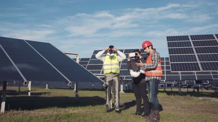 devise : Solar panel engineers using virtual reality headsets while planning expansion or other efforts outside for alternative energy Stock Footage